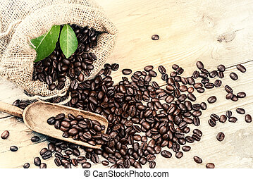 Roasted coffee beans with old wooden scoop. Food background