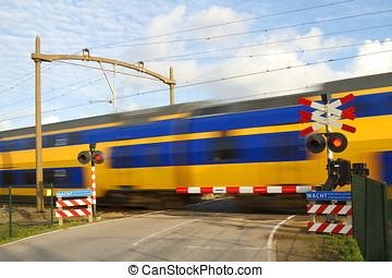 Dutch train passing a railway crossing - Dutch yellow and...