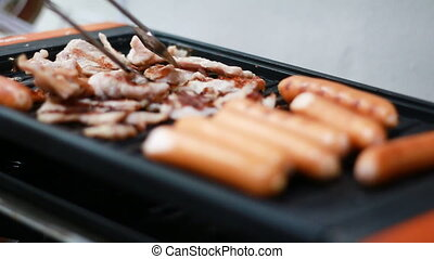 Close up shot of grilling sausage on electric hob with...