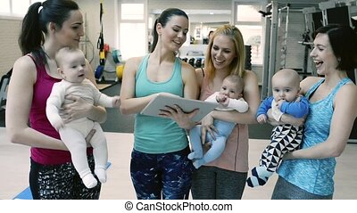 Mothers and babies in gym with personal trainer with tablet....