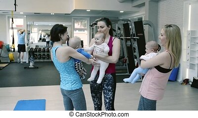 Mothers and babies in gym resting and talking. - Group of...