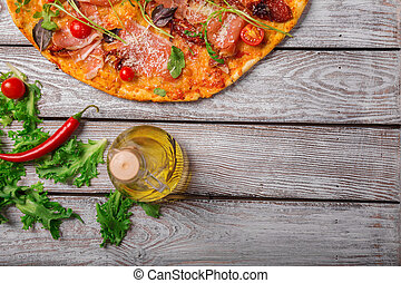 Italian pizza on a rustic table background, close-up. A half of meat pizza with salad leaves and olive oil. Copy space.
