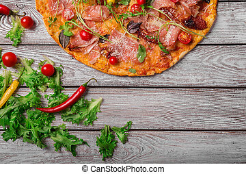 Italian pizza on a rustic table background, close-up. A half of meat pizza with salad leaves and hot chili pepper. Copy space.
