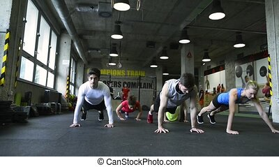 Young people in crossfit gym doing push ups. - Group of...