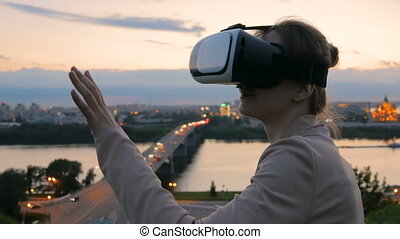 Woman uses virtual reality glasses in the city after sunset....