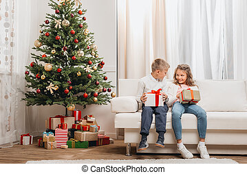 christmas morning - happy kids with christmas gifts sitting...