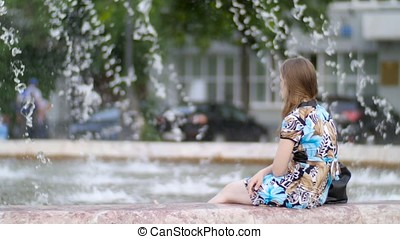 Girl sitting, in the background is a flowing fountain. Girl...
