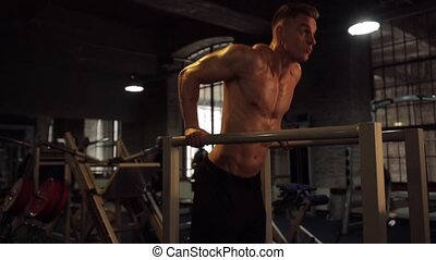man doing triceps dip on parallel bars in gym - fitness,...