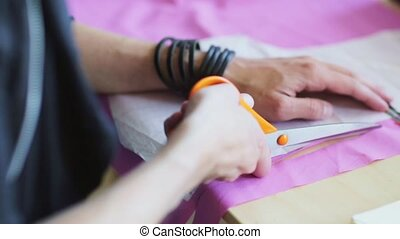 fashion designer hands cutting cloth with scissors - people,...