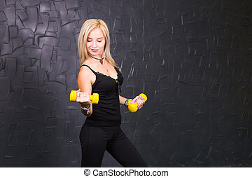 Attractive young fitness woman holding dumbell