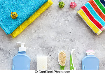 Preparation for spa therapy. Towels, soap, shampoo, lotion and brush on grey background top view copyspace