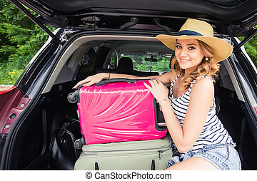 Happy woman with luggage in car trunk. Travel concept.