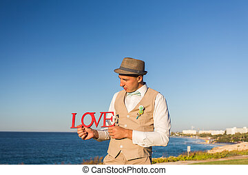 groom with wooden word LOVE in red colour