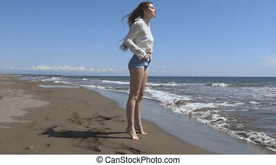 Beautiful young teen woman with blowing hair arms raised,...