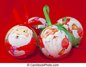 Christmas baubles with smiling Santas over red background