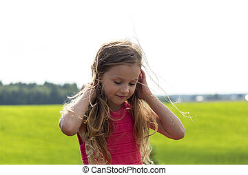 Cute pretty little girl on the nature background.