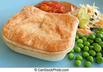 Mince meat pie served on a plate with pees, coleslaw salad...