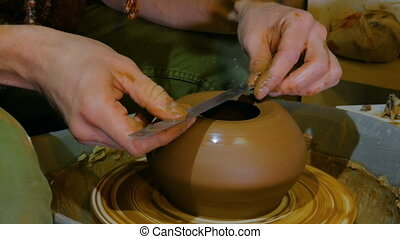 Professional potter shaping bowl with special tool in...