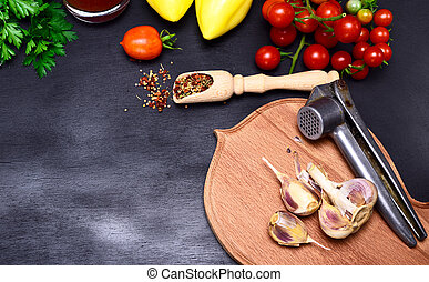 Fresh vegetables and garlic in the husk on a kitchen cutting...