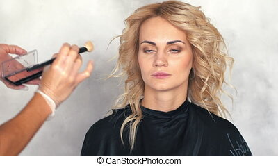 The make-up artist puts a blush on the face of a young...
