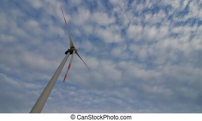 The blades of the wind station are spinning against the beautiful blue sky.