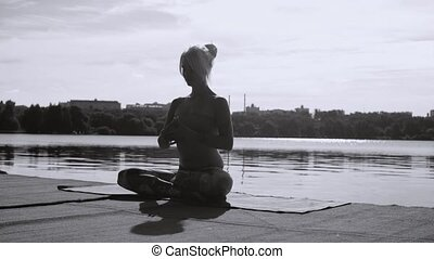 Young woman doing yoga exercises on the river bank -...