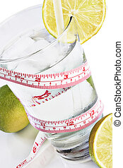 Water, limes and tape measure - Glass of water on a...