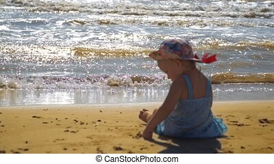 Little girl is sitting on a sandy beach and is painting on...
