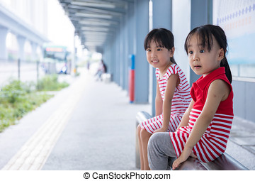 Asian Chinese little girls waiting for a bus