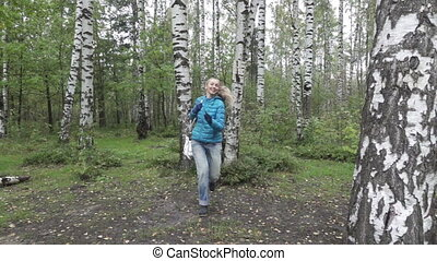 young woman with a long fair hair runs in the birch...