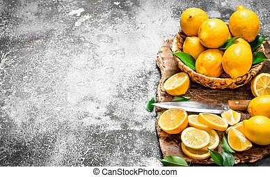 Fresh lemons in a basket with a knife on a cutting Board. On...