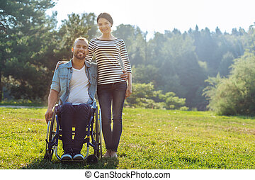 Wife and her husband with disabilities posing in meadow -...
