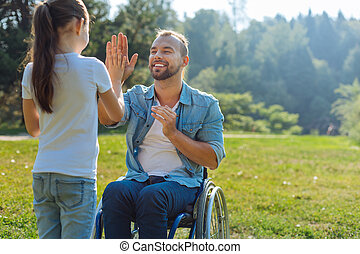 Little daughter giving her disabled father a high five -...