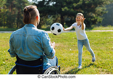 Incapacitated young man catching ball thrown by daughter -...