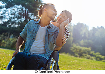 Smiling man with disabilities caressing his wifes cheek - I...