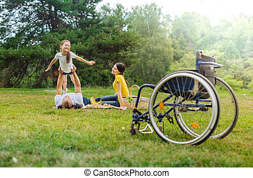 Joyful girl playing with her disabled dad lying on grass -...