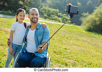Happy father with disabilities taking a selfie with daughter...