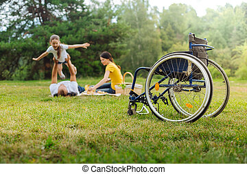 Disabled man lifting up his daughter on picnic - Play of...
