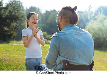 Little daughter playing pat-a-cake with her disabled father...