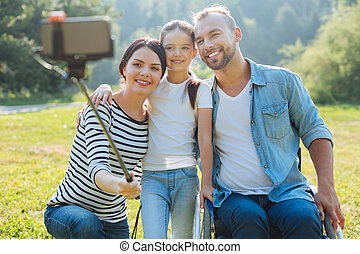Happy family taking a selfie together outdoors - Seizing the...