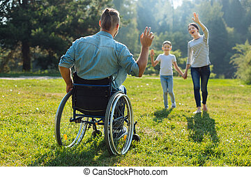 Young man with disabilities waving hello to his family - Hey...