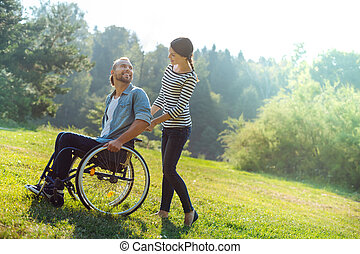 Caring wife carrying her disabled husband in a wheelchair -...