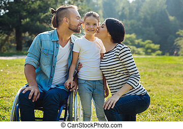 Lovely mother and father kissing their daughter on cheeks -...