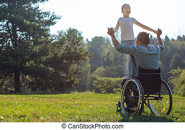 Mobility-impaired father holding his daughter on lap -...