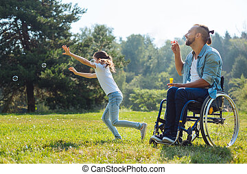 Cheerful disabled father and daughter playing with soap...