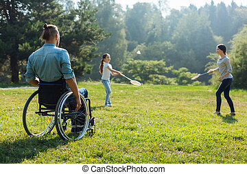 Young man in wheelchair watching his family play badminton -...