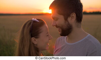 Charming young couple kissing in wheat field at sunset