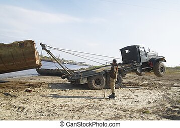 Disassembly of pontoon bridge - Truck is pulling element of...