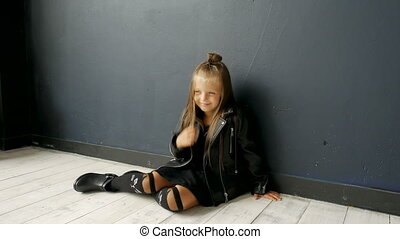 little girl model sitting on the floor