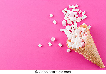 Marshmallows ice-cream and waffle cones on a pink background